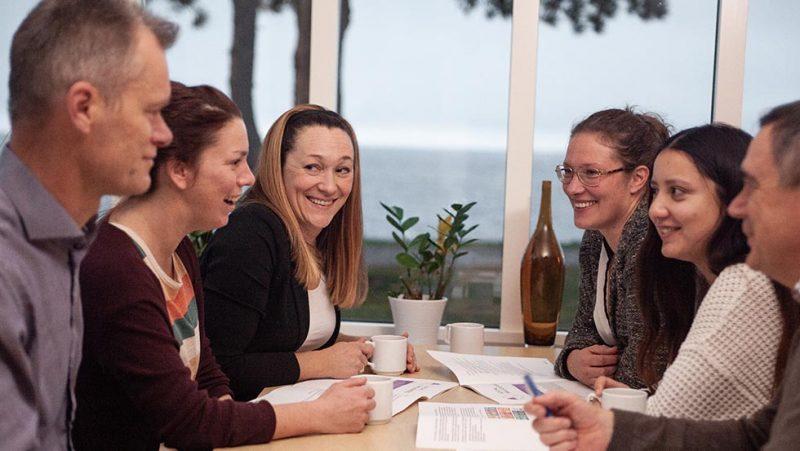 glada medarbetare samlade runt bord